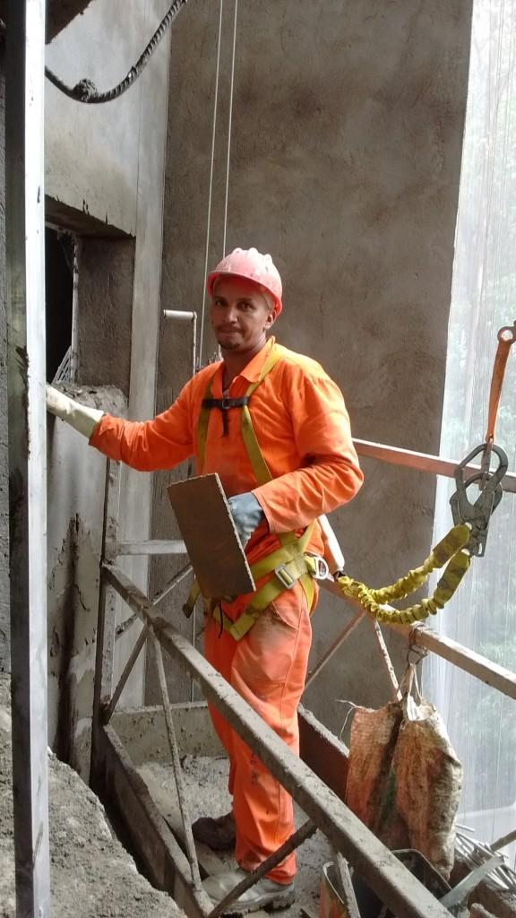 Colaborador em execução da fachada, com equipamentos de segurança